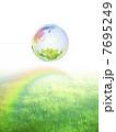 地球エコイメージ 虹のかかる草原に浮かぶ虹色の地球 7695249