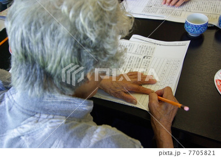 認知症予防の為に新聞活用講座で音読・書き写しをするお年寄り 7705821