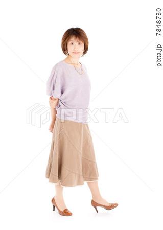 春夏ファッションで歩くポーズをする40代の女性 7848730