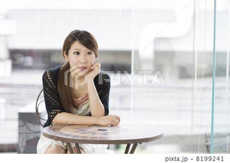 窓辺で頬杖をついて会話している若い女性 8199241