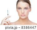 Unsmiling beautiful blonde holding surgical needle 8386447