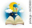 An open book with an image of a fairy and a sleeping moon 8423660