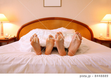 Woman and man rest on soft big bed with white sheets; focus on fの写真素材 [8448889] - PIXTA