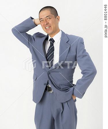 頭をかくスーツ姿の男性の写真素材