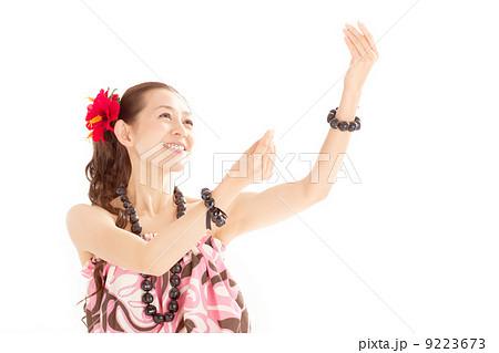 柔らかな手の動きが特徴的なフラのポーズで斜め上を見上げる笑顔が素敵な女性 9223673