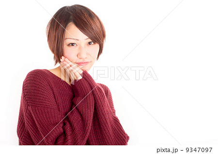 両手を頬の横で合わせて可愛らしくおねだりをする女の子 9347097