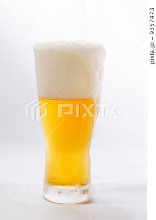 グラスビール ふちから泡がこぼれてたれて流れる 9357473