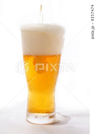 グラスビール 注いで泡がこぼれてたれて流れる 9357474