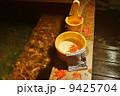 秋冬の素材・温泉の夜、湯桶の中にオオモミジの葉・横位置 9425704