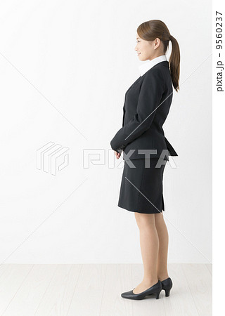 横を向くスーツ姿の女性(全身)...