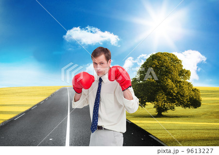 Composite image of businessman with his boxing gloves ready to f 9613227