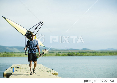 A middle-aged man carrying oars and a rowing shell on his shoulders, on a pontoon. 9702158