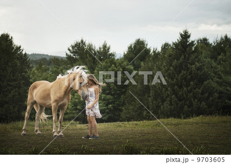 A young girl with a palomino pony in a field. 9703605
