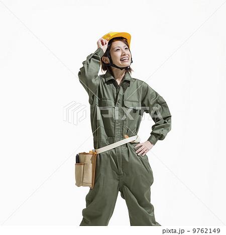 見上げる作業服姿の女性の写真素...