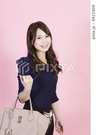 片手でバックを持つ笑顔の若い女性 9825806