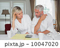 Couple sitting with home bills and calculator 10047020