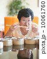 Senior Asian Woman dining at restaurant 10061760