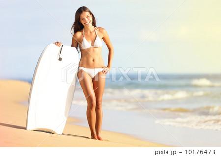 Surfer bikini woman on beach smiling with surfboard 10176473
