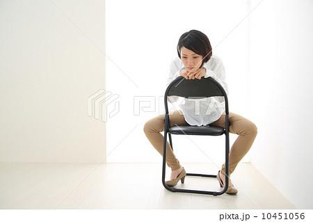 パイプ椅子に股がる女性 10451056