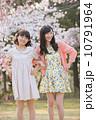 桜の木の下で春を楽しむ若い2人の女性 10791964