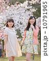 桜の木の下で春を楽しむ若い2人の女性 10791965
