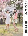 桜の木の下で春を楽しむ若い2人の女性 10791967