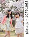 桜の木の下で春を楽しむ若い2人の女性 10791968