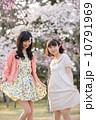 桜の木の下で春を楽しむ若い2人の女性 10791969