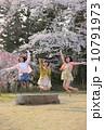 桜の木の下でジャンプする三人の若い女性 10791973
