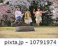 桜の木の下でジャンプする三人の若い女性 10791974