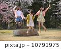 桜の木の下でジャンプする三人の若い女性 10791975