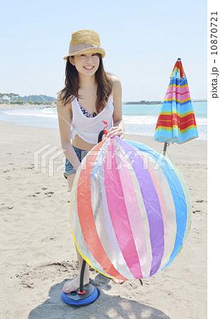 ビーチボールをを膨らませる若い女性 10870721