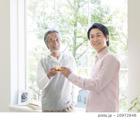 窓辺でグラスを交わす親子 10972646