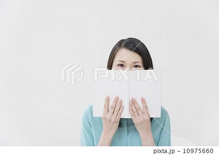 本で口元を隠す女性 10975660
