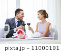 young couple with glasses of wine at restaurant 11000191
