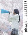 桜をバックにメガホンで応援をする高校生 11183326