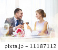 young couple with glasses of wine at restaurant 11187112