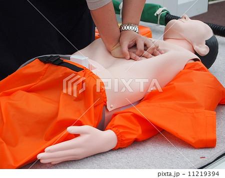 心臓マッサージを行う女性とAED 11219394