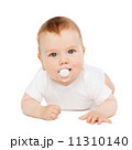 smiling baby lying on floor with dummy in mouth 11310140