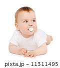 smiling baby lying on floor with dummy in mouth 11311495