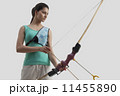 Female archer with bow and arrow isolated over gray background 11455890