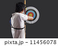 Rear view of man aiming target with bow against black background Rear view of man aiming target with bow against black background 11456078