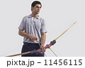 Young male archer with bow and arrow isolated over gray background 11456115