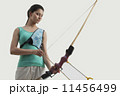 Portrait of female archer with bow and arrow isolated over gray background 11456499