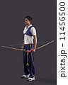 Full length of young male archer with bow and arrow over gray background 11456500