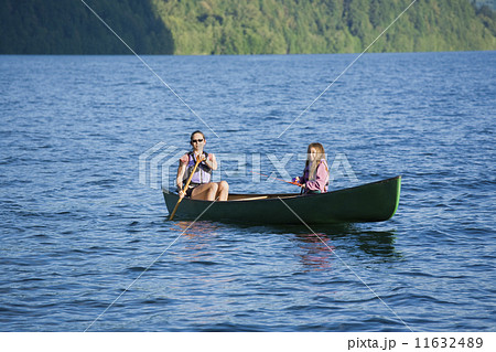 Asian mother and daughter rowing in canoe 11632489