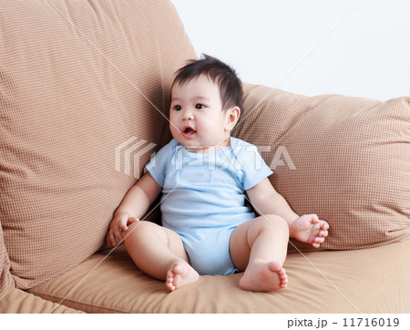 Thai pretty baby sitting and smiling on the sofa 11716019