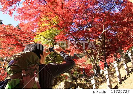 大山の紅葉を撮る登山者 11729727