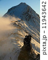 夕暮れ迫る地吹雪の八ヶ岳稜線の岩峰と赤岳 11943642