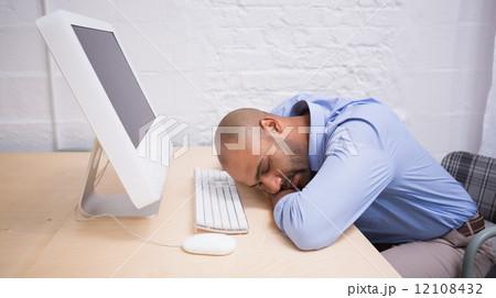 Businessman sleeping by computer at deskの写真素材 [12108432] - PIXTA